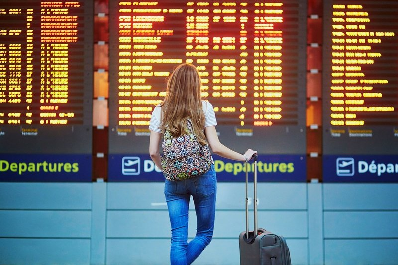 woman looking at departures board - travel budget example