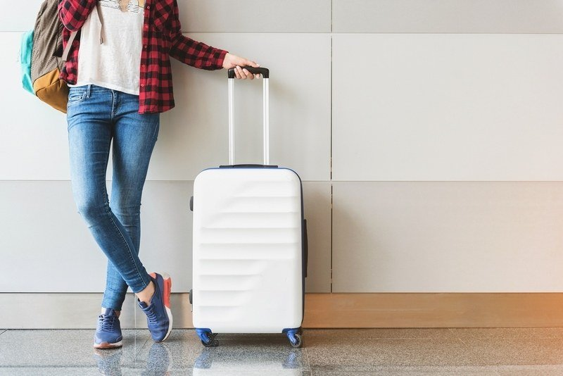 how to pack carry on only - woman with suitcase