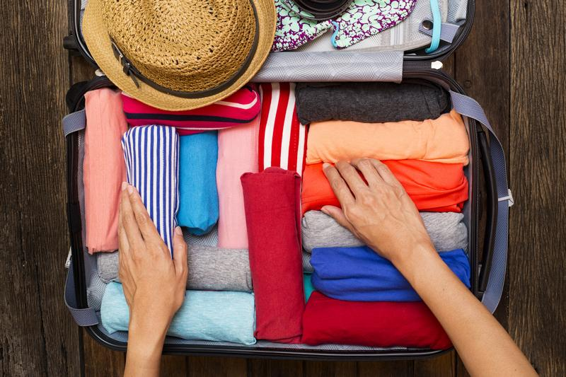 how to travel with only cabin baggage - clothing being packed into a suitcase