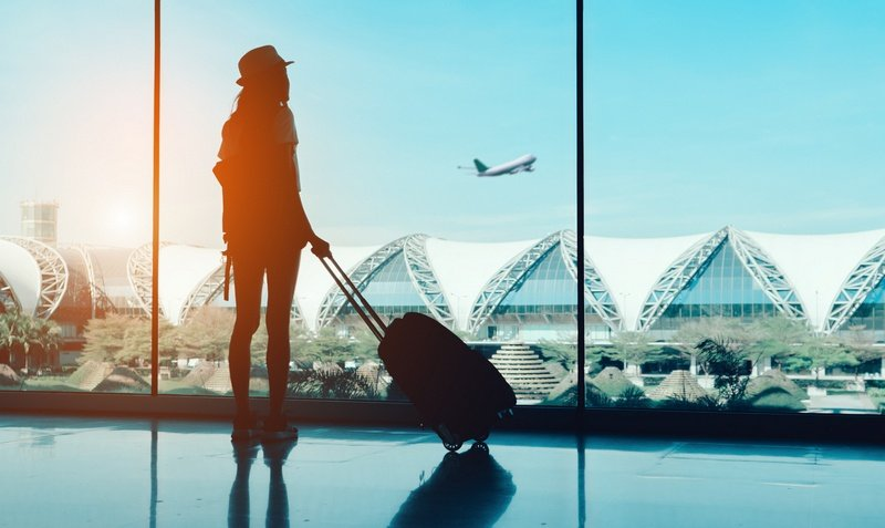 woman on a layover in the airport with suitcase watching a plane take off